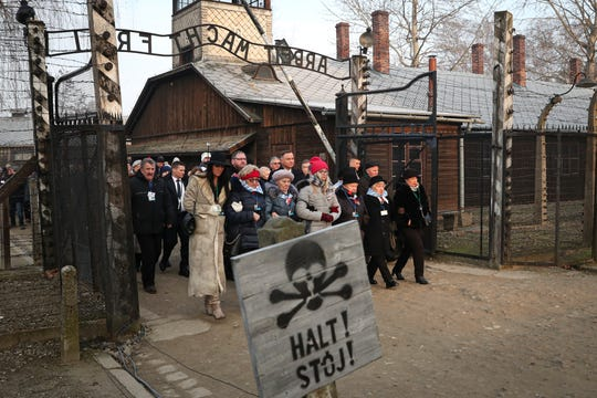 Poland's President Andrzej Duda walks along with survivors through the gates of the Auschwitz Nazi concentration camp to attend the 75th anniversary of its liberation in Oswiecim, Poland, Monday.