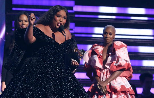 "Lizzo accepts the award for best pop solo performance for ""Truth Hurts"" at the 62nd annual Grammy Awards on Sunday in Los Angeles. Looking on at right is Cynthia Erivo."