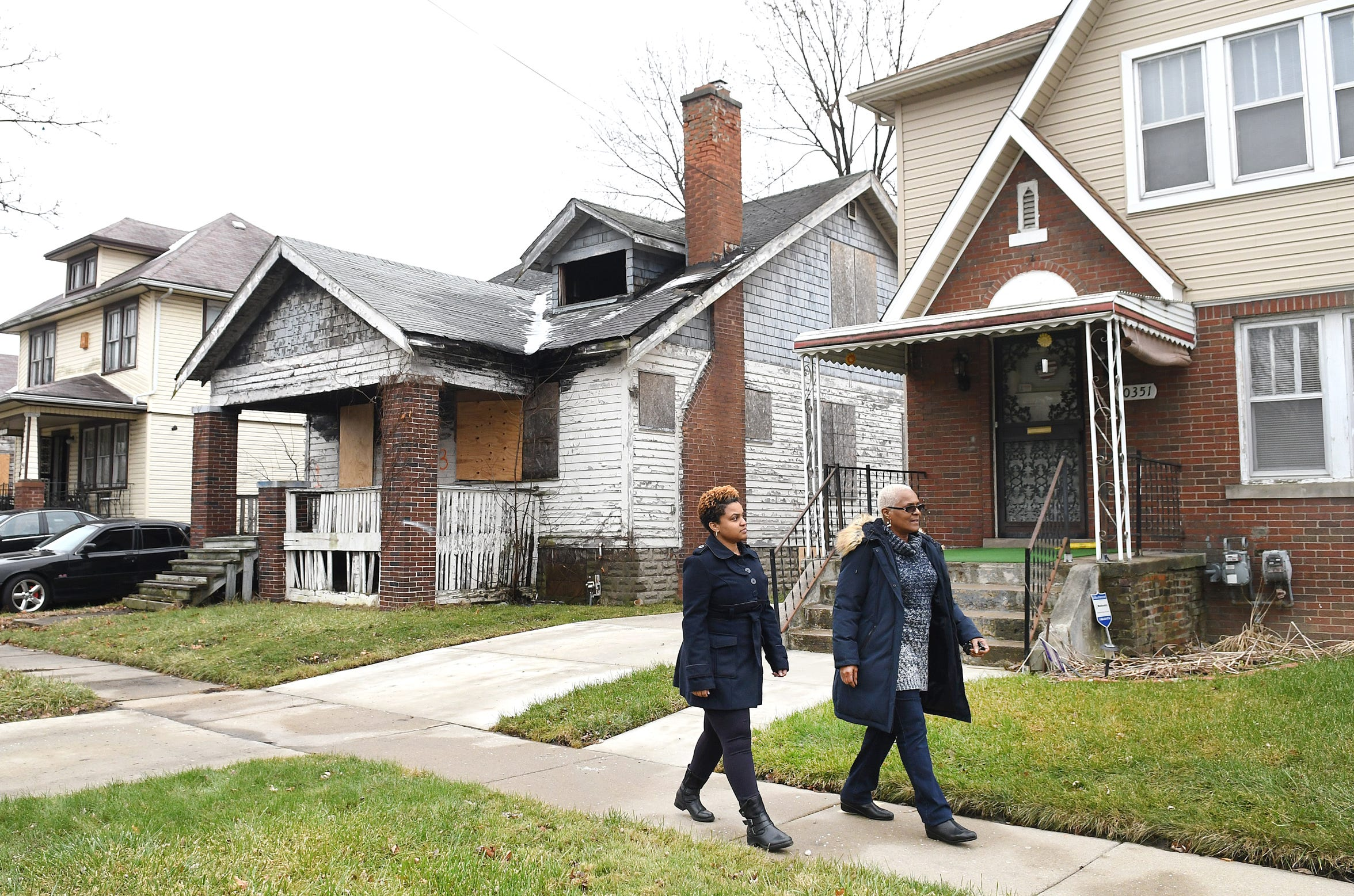 Jackie Smith of Detroit and her daughter, Kellie, walk outside their family home in Detroit passing a long-vacant house (at left) that Jackie has been trying to get knocked down and cleared away.