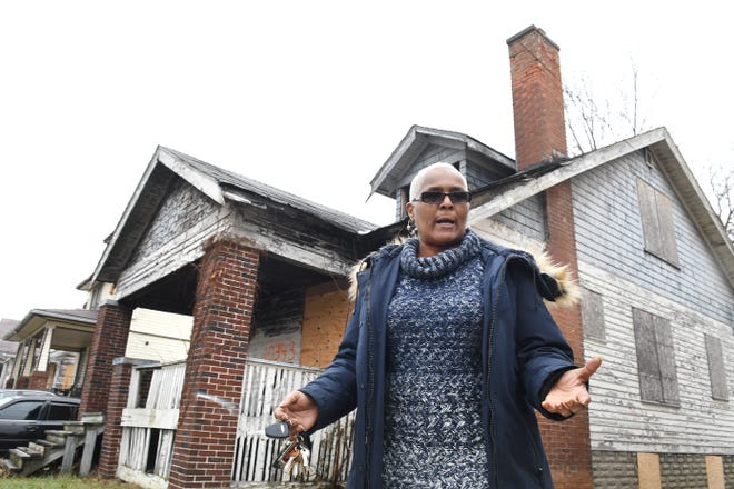 Jackie Smith of Detroit is concerned about the vacant boarded up house (background) next to her home in Detroit and has been trying to get it demolished and cleared away.