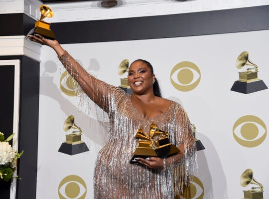 """Lizzo poses in the press room with the awards for best pop solo performance for """"Truth Hurts,"""" best urban contemporary album for """"Cuz I Love You"""" and best traditional R&B performance for """"Jerome"""" at the 62nd annual Grammy Awards."""