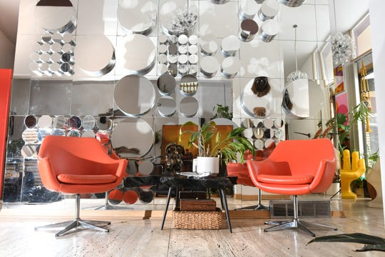 A 1960s multi-angled mirror wall by John Leslie, a Cranbrook graduate, is framed by two orange chairs at the Elliott family home in Southfield.