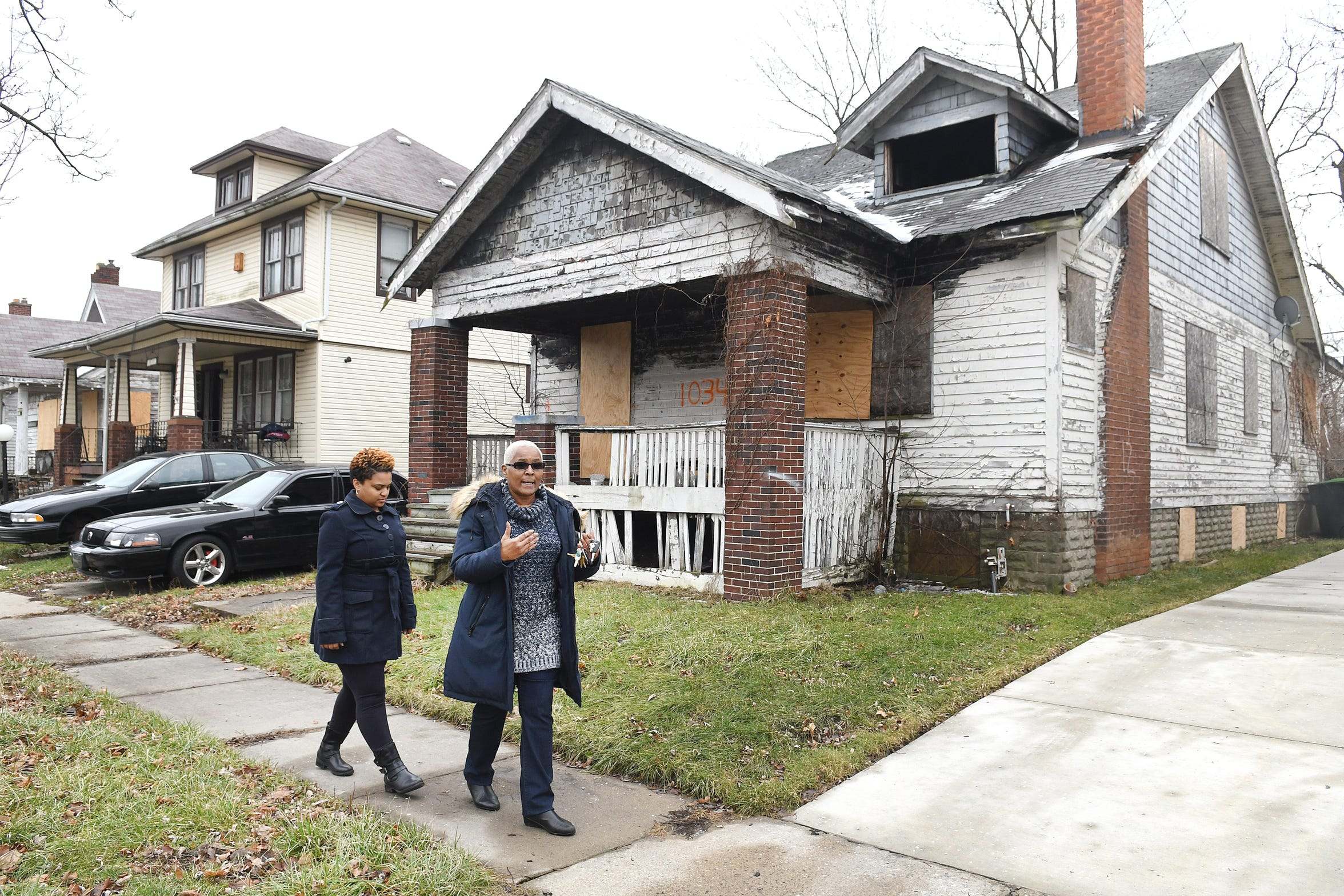 Kellie Smith and her mother Jackie Smith of Detroit walk past a long-vacant house in their neighborhood. Jackie has been trying to get the house demolished