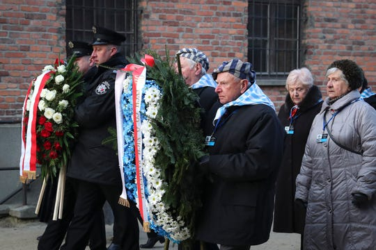 Survivors carry a wreath at the Auschwitz Nazi death camp in Oswiecim, Poland, Monday.