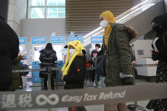 Passengers wear masks in a departure lobby at Incheon International Airport in Incheon, South Korea, Monday, Jan. 27, 2020.