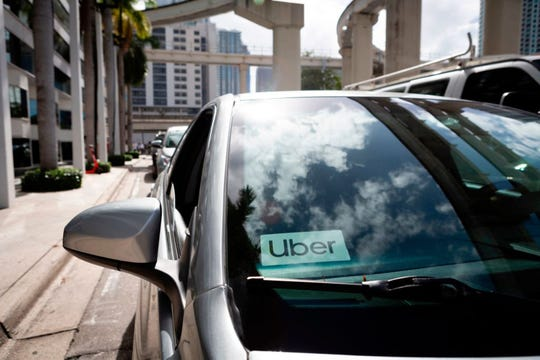An Uber sticker is seen on a car windshield on the street in downtown Miami on January 9, 2020. (EVA MARIE UZCATEGUI/AFP via Getty Images/TNS)