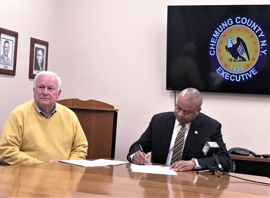 Chemung County Executive Christopher Moss, joined by Deputy County Executive David Sheen, signs an executive order Monday directing that all public meetings in county-owned facilities be carried on webcast.