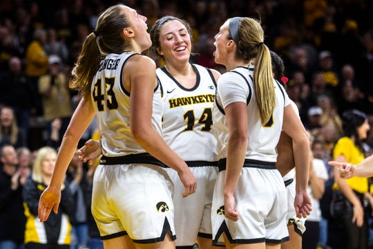 Iowa's McKenna Warnock (14) gets embraced by teammates Amanda Ollinger (43) and Makenzie Meyer, right, after drawing a foul during a NCAA Big Ten Conference women's basketball game, Sunday, Jan. 26, 2020, at Carver-Hawkeye Arena in Iowa City, Iowa.