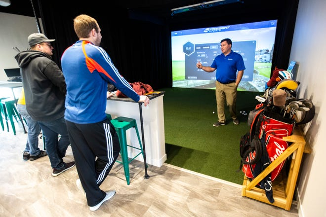 Austin Kopp gives instructions at a simulator bay, Saturday, Jan. 25, 2020, at Golfletics in Coralville, Iowa.