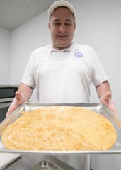 Robert Page holds a tray of freshly made coconut brittle Monday, Jan. 27, 2020 in the new storefront for Granny's Confections, relocating recently from the previous Hartland Township store.