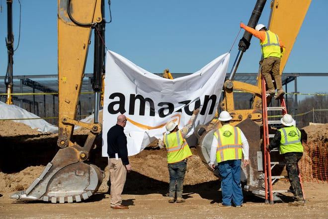 Workers take down a banner Monday, Jan. 27, 2020, after a groundbreaking ceremony for a new Amazon fulfillment center in Memphis.