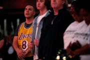 David Moulton of Memphis, wearing a jersey autographed by the late Kobe Bryant, looks up during a moment of silence for Bryant at Sunday's Grizzlies game.
