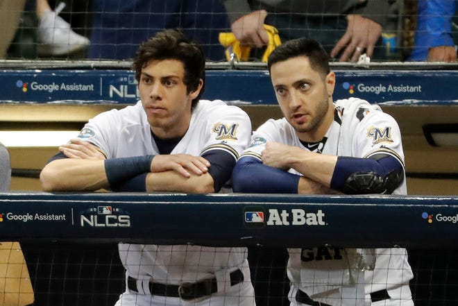 Milwaukee Brewers outfielders Christian Yelich and Ryan Braun watch during Game 7 of the 2018 NLCS against the Los Angeles Dodgers.