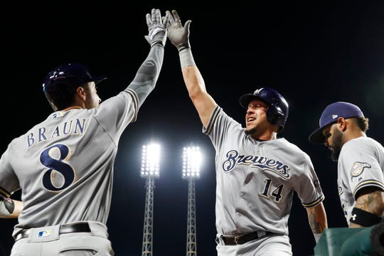 Hernan Perez (14) celebrates with Ryan Braun in game against the Cincinnati Reds in 2018.