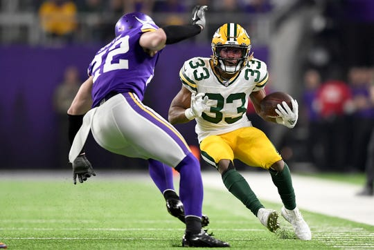 Running back Aaron Jones (33) of the Green Bay Packers carries the ball against free safety Harrison Smith (22) of the Minnesota Vikings during a game  at U.S. Bank Stadium on Dec. 23 in Minneapolis.