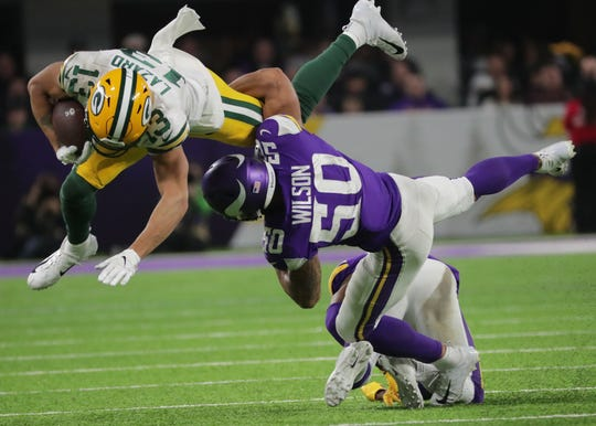 Packers wide receiver Allen Lazard (13) makes a first down while being tackled by Vikings linebacker Eric Wilson (50) during the third quarter of their December 2019 game at US Bank Stadium in Minneapolis.