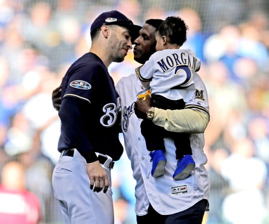 Nyjer Morgan is greeted by Ryan Braun after Morgan threw out the ceremonial  first pitch before Game 1 of the National League Division Series between the  Brewers and Rockies. It was a special moment because Morgan drove in the winning run in the 10th inning of final game of the Brewers' previous NLDS appearance in 2011.