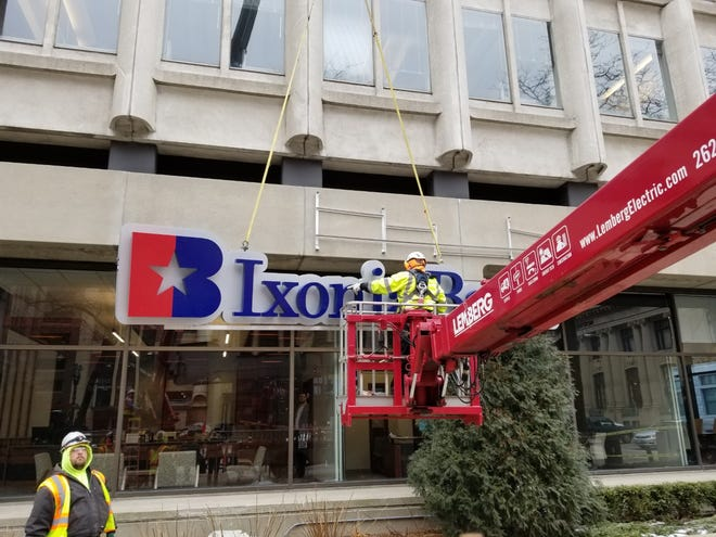 An Ixonia Bank sign goes up on the FoxconnÕs North American Headquarters at 611 E. Wisconsin Ave on Monday.