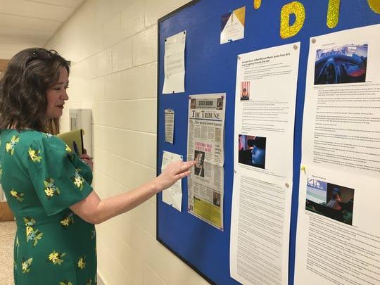 Indiana Digital Learning School's head of school Elizabeth Sliger checks a bulletin board containing good news about the school.