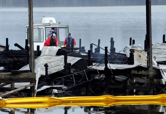 A crew looks at the charred remains of a boat following a fatal fire at a Tennessee River marina in Scottsboro, Ala., on Monday, Jan. 27, 2020. First responders had to rescue people from the water, and fire officials said it may take days to go through sunken boats that could hold additional victims. (AP Photo/Jay Reeves)