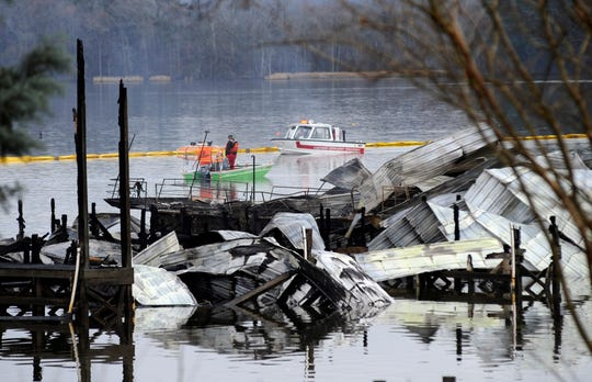 People on boats patrol near the charred remains of a dock following a fatal fire at a Tennessee River marina in Scottsboro, Ala., Monday, Jan. 27, 2020. Authorities said the explosive fire was reported overnight while people were sleeping on boats tied up at the structure. (AP Photo/Jay Reeves)