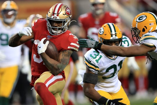 49ers running back Raheem Mostert avoids Packers defenders to score a touchdown during the NFC championship game Jan. 19.