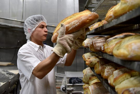 Anthony and Sons Bakery produces over 10,000 loaves of bread daily in their Denville factory. Producing hundreds of products and artisan specialties. A worker removes hot loaves of Pane di Casa and places them on a cooling rack.