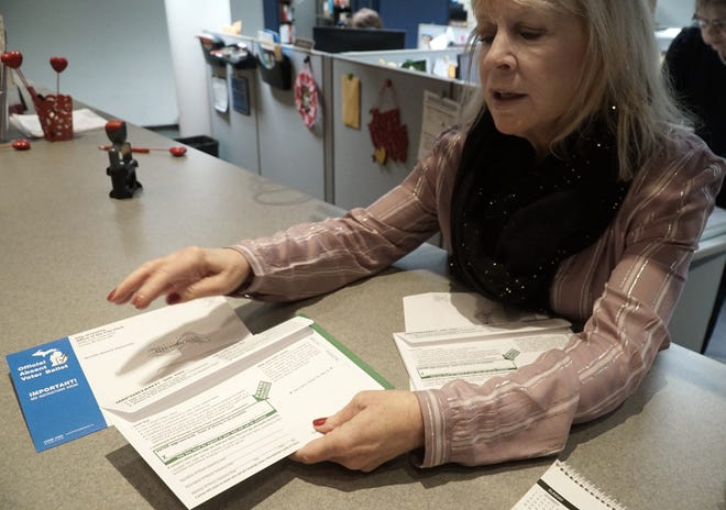 Livonia will be mailing out absentee ballots in new envelopes this voting season. Here, Bonnie Murphy, secretary to City of Livonia Clerk Susan Nash, displays the new-look absentee envelopes on Jan. 27, 2020.