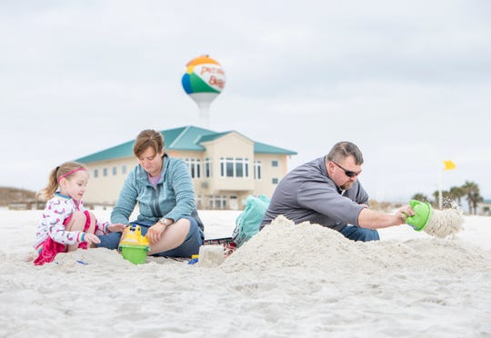 Dolly Cole, 5, of Owensboro, Kentucky, and her parents Kelita and Wesley play in the sand at Pensacola Beach on Monday, Jan. 27, 2020.