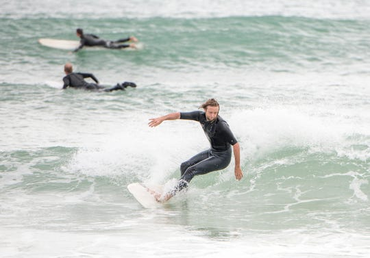 Chance Wallis of Gulf Breeze and others surf at Pensacola Beach on Jan. 27.