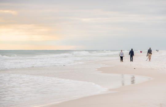 People walk along the surf at Pensacola Beach on Monday, Jan. 27, 2020.