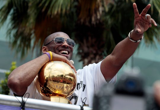 FILE - In this June 21, 2010, file photo, holding the NBA championship trophy, Los Angeles Lakers' Kobe Bryant flashes the victory sign during a parade in downtown Los Angeles. Bryant, the 18-time NBA All-Star who won five championships and became one of the greatest basketball players of his generation during a 20-year career with the Los Angeles Lakers, died in a helicopter crash Sunday, Jan. 26, 2020. (AP Photo/Richard Vogel, File)