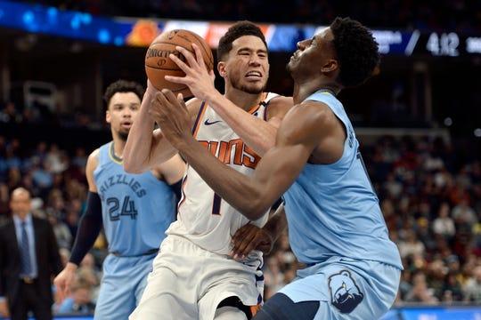 Phoenix Suns guard Devin Booker (1) drives against Memphis Grizzlies forward Jaren Jackson Jr., right, in the second half of an NBA basketball game Sunday, Jan. 26, 2020, in Memphis, Tenn. (AP Photo/Brandon Dill)