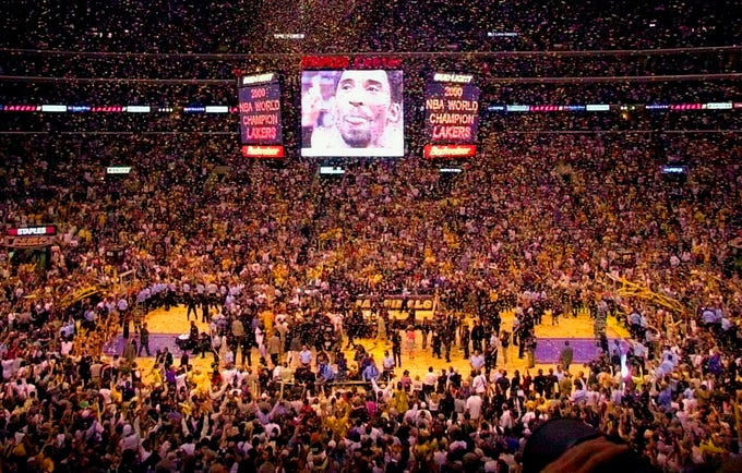 FILE - In this June 19, 2000, file photo, Los Angeles Lakers' Kobe Bryant's image overlooks the Staples Center arena after the Lakers won the NBA Championship against the Indiana Pacers in Los Angeles. Bryant, the 18-time NBA All-Star who won five championships and became one of the greatest basketball players of his generation during a 20-year career with the Los Angeles Lakers, died in a helicopter crash Sunday, Jan. 26, 2020. (AP Photo/Michael Caulfield, File)