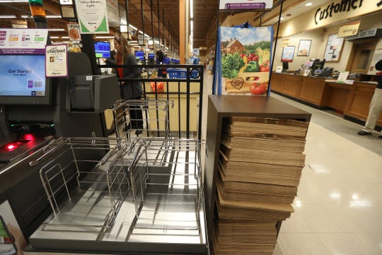 The holder for plastic bags at the self checkout is now empty with paper bags in its place at the Pittsford Wegmans.
