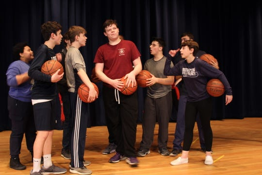 "Colin Quattrini, as Troy Bolton, is surrounded by his teammates who are encouraging him to ""Get Your Head in the Game,"" at a recent rehearsal for Brighton High School's presentation of ""High School Musical."""