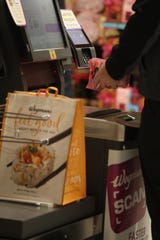 Peter Platt of Brighton checks out his groceries to put in a reusable bag Pittsford Wegmans.