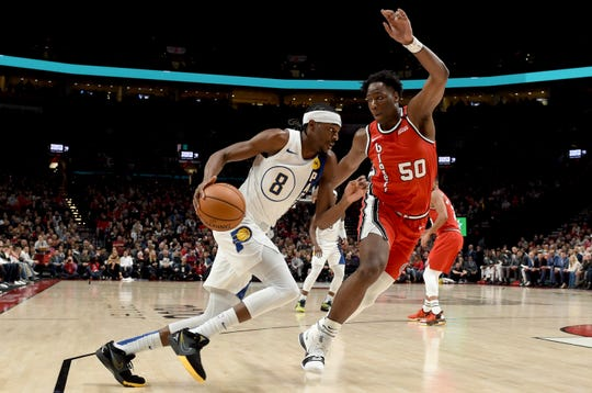 Indiana Pacers forward Justin Holiday, left, drives to the basket on Portland Trail Blazers forward Caleb Swanigan, right, during the first half of an NBA basketball game in Portland, Ore., Sunday, Jan. 26, 2020.