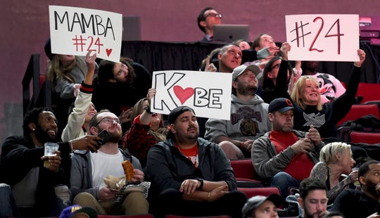 Fans hold up signs in memory of Kobe Bryant, who was killed in a helicopter crash in California, during the second half of an NBA basketball game between the Portland Trail Blazers and the Indiana Pacers in Portland, Ore., Sunday, Jan. 26, 2020. The Blazers won 139-129.