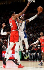 Indiana Pacers guard Aaron Holiday, right, drives to the basket on Portland Trail Blazers center Hassan Whiteside, left, during the first half of an NBA basketball game in Portland, Ore., Sunday, Jan. 26, 2020.