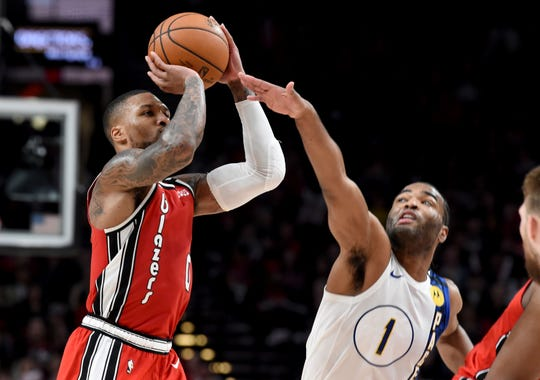 Portland Trail Blazers guard Damian Lillard, left, shoots the ball over Indiana Pacers forward T.J. Warren, right, during the second half of an NBA basketball game in Portland, Ore., Sunday, Jan. 26, 2020. Lillard scored 50 points as the Blazers won 139-129.