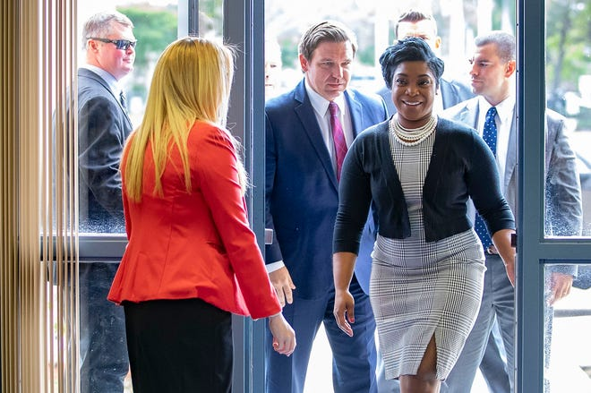 Omni Middle School principal, Nikkia DeLuz, leads Gov. Ron DeSantis into a press conference at the school to announce a partnership with the Marcus Foundation to expand opportunities for high school students to compete in speech and debate statewide and to provide more of those classes in middle schools.