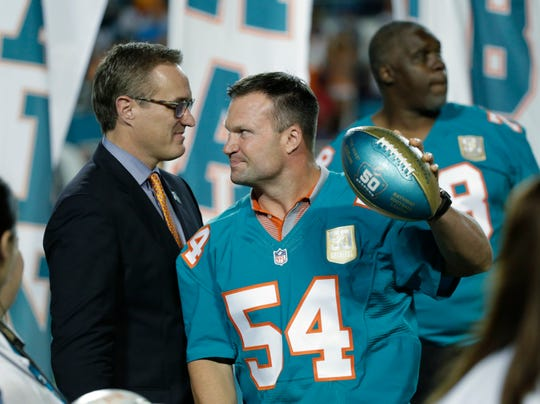 Former Miami Dolphins player Zach Thomas (54) is presented a football by Dolphins president and CEO Tom Garfinkel during the Dolphins All-Time 50th Anniversary Team ceremony during halftime of a game Dec. 14, 2015, in Miami Gardens, Fla.