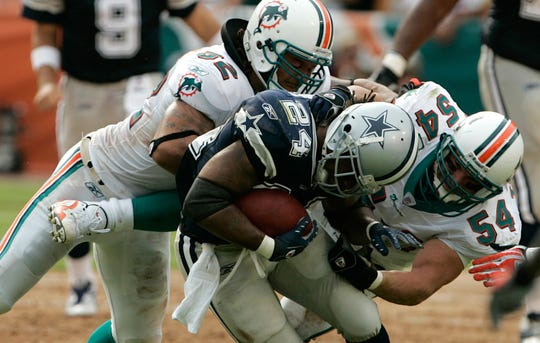 Dallas Cowboys running back Marion Barber (24) is tackled by Miami Dolphins linebackers Zach Thomas (54) and Channing Crowder, left, in the second quarter during a game in Miami on Sunday, Sept. 16, 2007.
