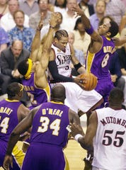 Allen Iverson of the 76ers, center, tries to get a shot off against the Los Angeles Lakers' Kobe Bryant, right, during Game 4 of the 2001 NBA Finals.