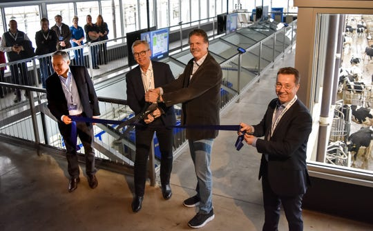 Joakim Rosengren, president and CEO of DeLaval, second from left, and Mike McCloskey, co-founder of Fair Oaks Farms, second from right, during a ribbon cutting ceremony in November 2019 to announce the opening of a new robot barn and visitor area at the dairy facility.
