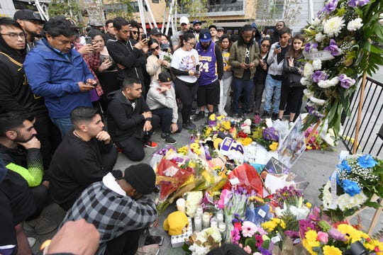 People gather at a makeshift memorial near Staples Center Jan. 26, 2020, after the death of Laker legend Kobe Bryant.