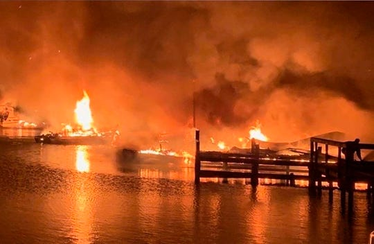 A fire burns on a dock where at least 35 vessels, many of them houseboats, were destroyed by fire early Monday, Jan. 27, 2020, in Scottsboro, Ala.