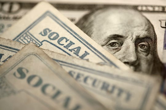 Several Social Security cards rest on top of a $100 bill.