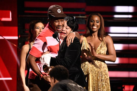 Tyler, The Creator hugs his mom as he accepts the award for best rap album during the 62nd annual Grammy Awards
